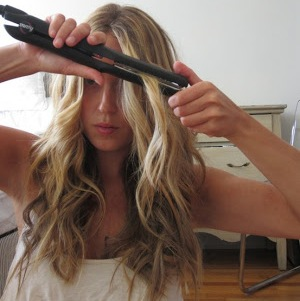 A woman using hair flat iron